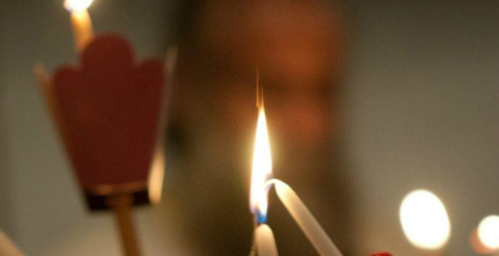 person lighting white candle