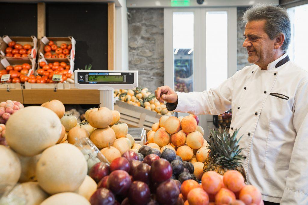 chef in front of fruits during daytime