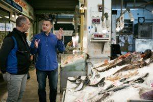 two men talking beside fish inside room