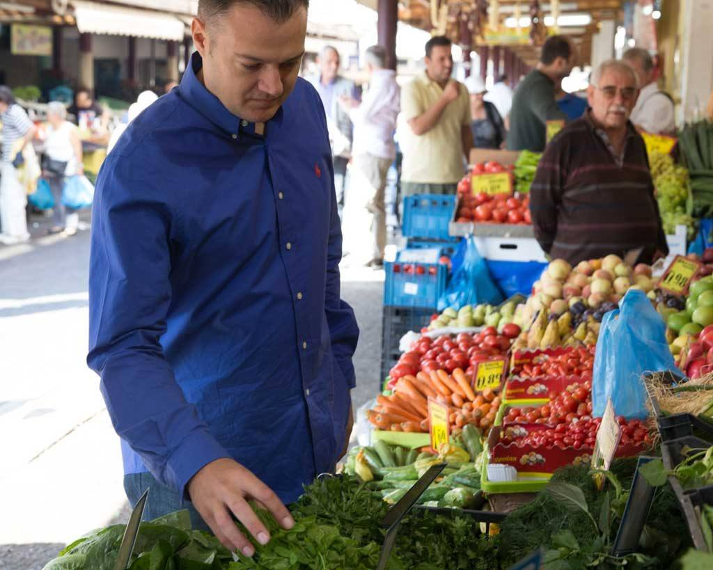 man holding green spinach at market