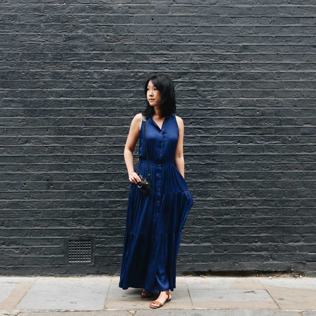 woman standing with hands on pocket near concrete wall