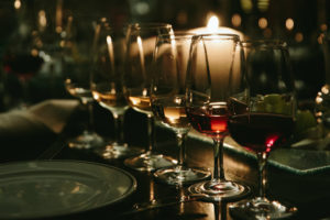 wine glasses lined on table with candle