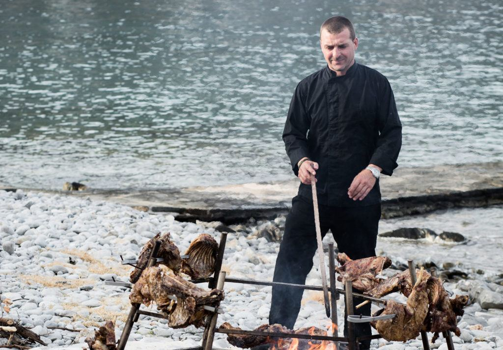 man barbecuing meat near beach