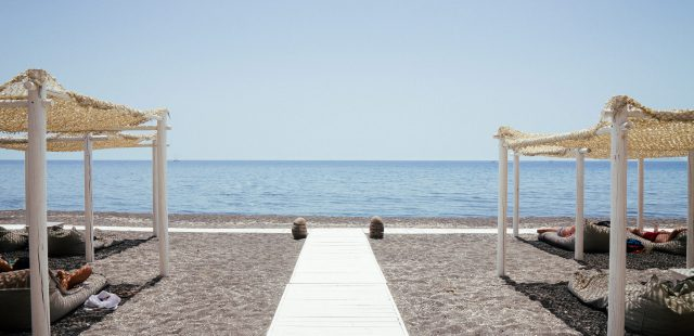 two white wooden hats beside calm sea at daytime