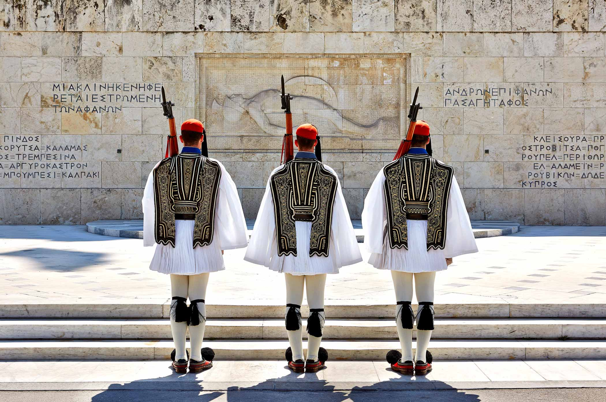 three monarch soldiers standing facing concrete wall