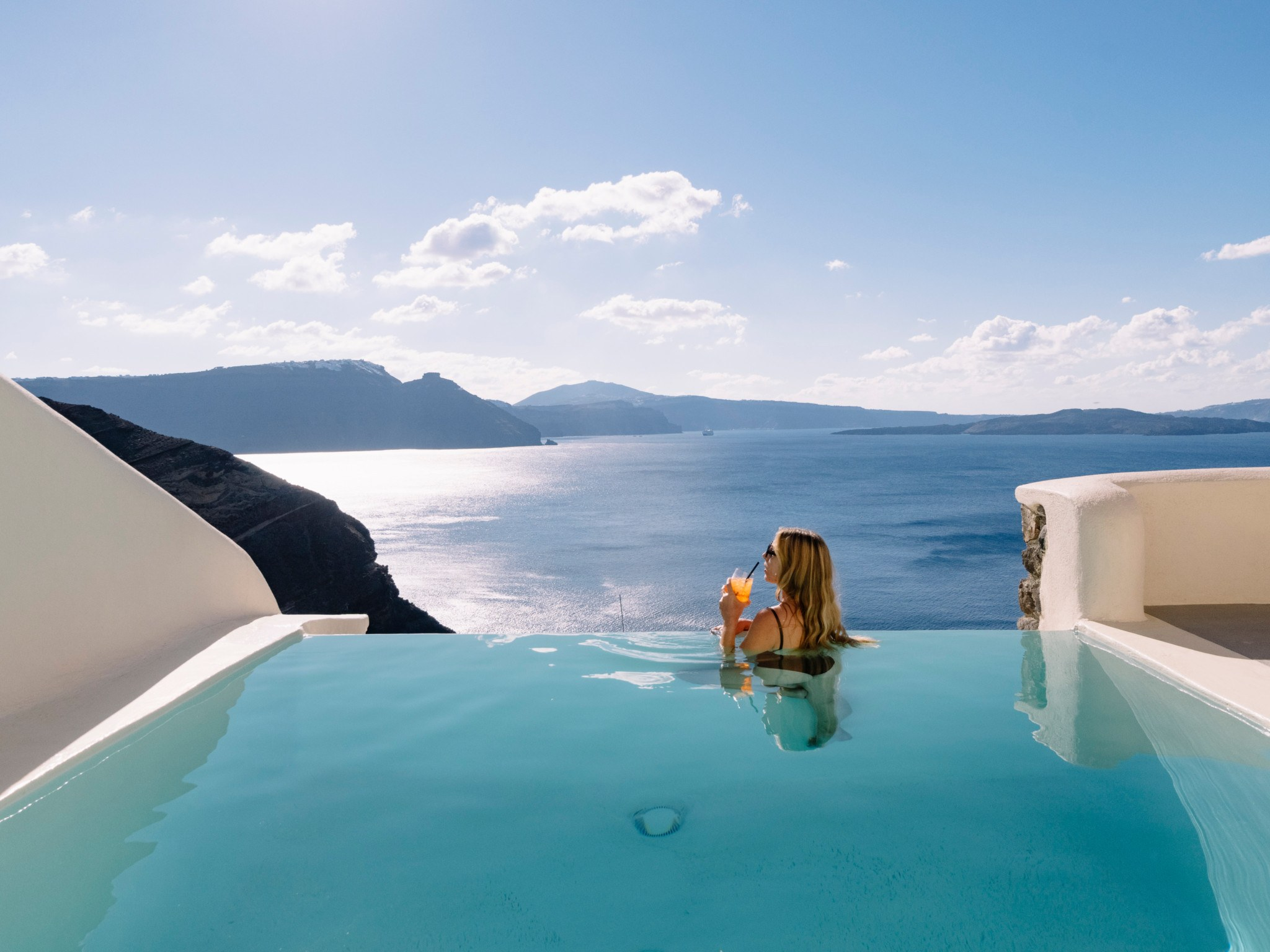 woman sipping drink on infinity pool