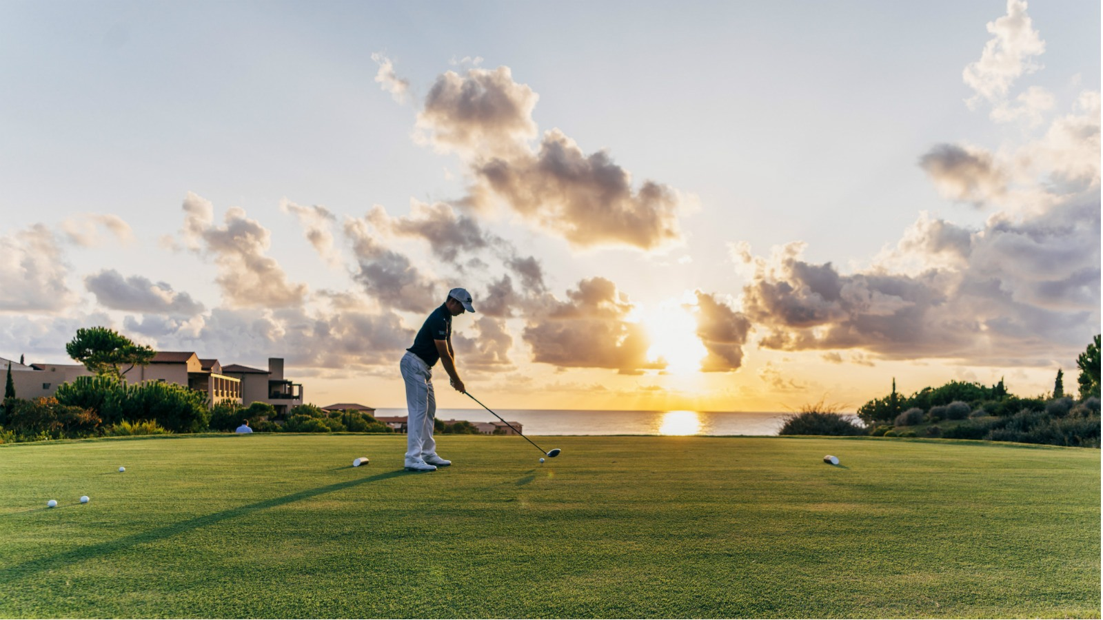 man playing golf during golden hour