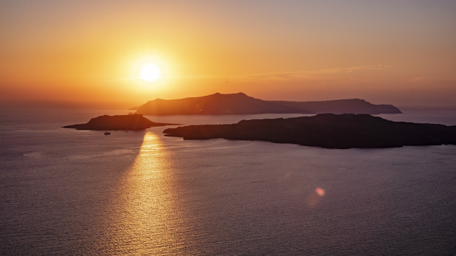 mountain range surrounded by calm sea at golden hour