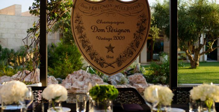 a Dom Pérignon sign over a table set with flower centerpieces outside in the day time
